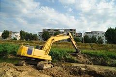 Excavatrice jaune excavant sur le lit de la rivière Photo libre de droits