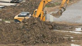 Excavatrice jaune sur un chantier de construction en été clips vidéos