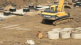 Excavatrice jaune sur un chantier de construction en été banque de vidéos