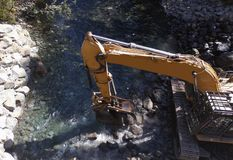 Excavatrice Moving Rocks en rivière images stock