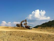 Excavatrice nivelant la terre photographie stock