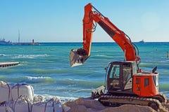 Excavatrice orange sur la plage de la ville fran?aise de Cannes dans la perspective de la mer bleue photos libres de droits