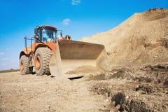 Excavatrice orange sur un chantier de construction Image libre de droits