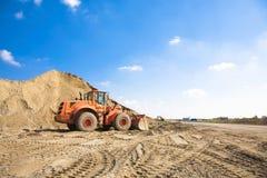 Excavatrice orange sur un chantier de construction Photos stock