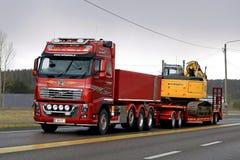 Excavatrice rouge de chenille de transports de Volvo FH16 750 le soir Image stock