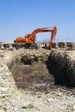 Excavatrice sur le bord de la piqûre Photographie stock
