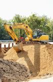 Excavatrice sur un grand tas Images stock