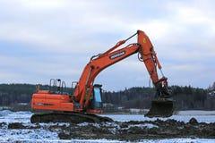 Excavatrice Working au projet de construction en hiver Photographie stock libre de droits