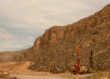 Excavatrices et tracteurs sur la route dans le désert vers grand Photographie stock libre de droits