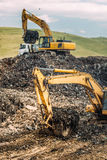 Excavatrices résistantes chargeant des camions de déchargeur avec des déchets et des déchets urbains Image stock