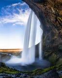 Excave detrás de la cascada de Seljalandsfoss en Islandia con Exposu largo fotos de archivo