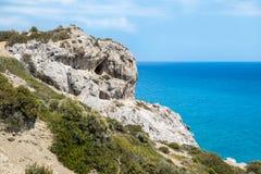 Excave en una montaña rocosa con los arbustos verdes en una costa costa imagenes de archivo