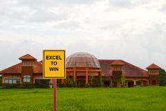 Excel to win. In a school house with green grassland and stormy sky royalty free stock photography