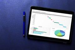Excelez le concept de tableau de bord de projet sur l'écran de comprimé avec le stylo bleu sur le modèle bleu image stock