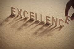 EXCELLENCE wood word. On compressed board with human`s finger at E letter royalty free stock image