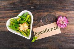 Excellence word on card. With dried flower and heart shape bowl on wood stock photo
