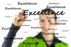 Excellence. Young female writing word Excellence on virtual screen royalty free stock images