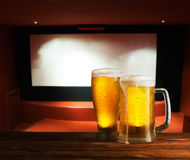 Excellent beer on a wooden table. Against the background of a movie screen royalty free stock image