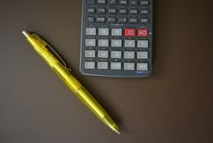 Gray calculator and a yellow pen on a brown matte background. Excellent bright photos for stores for articles and magazines and any glosses made to order royalty free stock photo