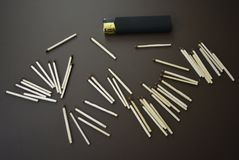 Scattered new matches with a black lighter on a brown matte background stock photos