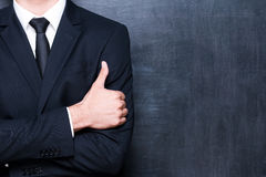 Excellent!. Close-up of man in formalwear showing his thumb up while standing against blackboard Stock Image