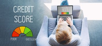 Excellent Credit Score with man using a laptop. In a modern gray chair stock photography