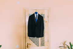 Excellent expensive black wedding suit hanging in the interior Stock Photos