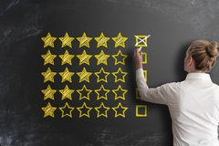 Excellent five star customer feedback or client service rating. With rear view of woman at blackboard stock photo