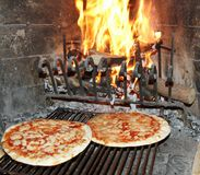 Excellent fragrant pizza baked in a wood fireplace with a wood-b Royalty Free Stock Photography