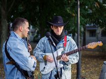 Happy young guys sings songs and plays guitar on a jeans jacket in a park on a natural background. An excellent handsome boys with a black hat plays the guitar royalty free stock images