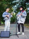 Happy young guys sings songs and plays guitar on a jeans jacket in a park on a natural background. An excellent handsome boys with a black hat plays the guitar stock photo