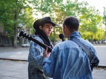 Happy young guys sings songs and plays guitar on a jeans jacket in a park on a natural background. An excellent handsome boys with a black hat plays the guitar royalty free stock photo