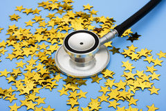 Excellent Healthcare. A pile of gold stars and stethoscope on a blue background, excellent healthcare stock image