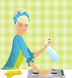 Excellent means. Beautiful housewife washing the gas stove by means of a miracle Royalty Free Stock Images