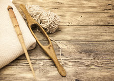 Excellent mocap two old wooden spindle with a ball of wool thread for the manufacture of woolen threads on a wooden background Stock Photography