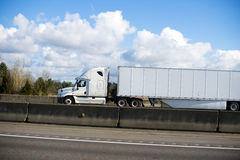 Excellent modern white semi truck trailer dry van on highway wit Royalty Free Stock Photos