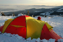 Excellent prospects!. Winter expedition in the mountains. Man looking out of his tent in the early morning. He has a superb view. It seems to be a great day Royalty Free Stock Photos