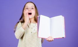 She is excellent in reading. Happy little girl enjoy reading books. Cute small child happy smiling with open book for stock photos