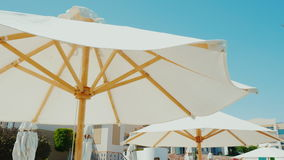 Excellent rest in a luxury hotel. A row of snow-white umbrellas against the blue sky background. Steadicam shot stock video