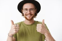 Excellent. Satisfied and supportive charming young boyfriend with beard and pierced nose smiling delighted as giving. Thumbs up in approval and like, cheering stock photos