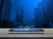 Business customer service evaluation and feedback rating concept. Excellent smiley face rating icon on modern smart mobile phone screen on wooden table over stock image