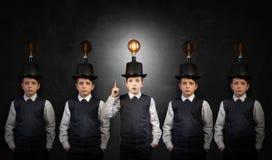 Excellente idée, enfant avec l'ampoule d'edison au-dessus de sa tête atanding hors de la foule photo stock
