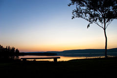 An Exceptional Seat. Cape Breton Coast during Sunset with Seating Bench and Tree in Silhouette Royalty Free Stock Photography