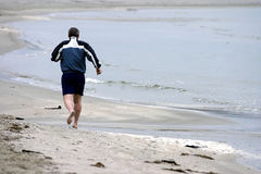 Excercise By The Beach. Middle aged man jogging by the beach Stock Photos