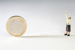 Excercising The Right To Veto. A miniature figurine with his hand in the air facing a Euro coin, conceptual of the UK veto of the EU bailout and restructuring Stock Image