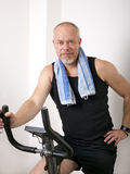 Excersising. Man excersising at home on bicycle Royalty Free Stock Images