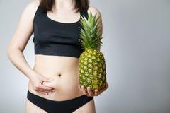 Exceso de peso de las mujeres con la piña foto de archivo libre de regalías