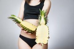 Exceso de peso de las mujeres con la piña imagen de archivo