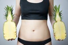 Exceso de peso de las mujeres con la piña foto de archivo
