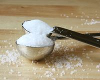Excess Salt. Granulated salt and course kosher salt spilling over in measuring spoons royalty free stock photos